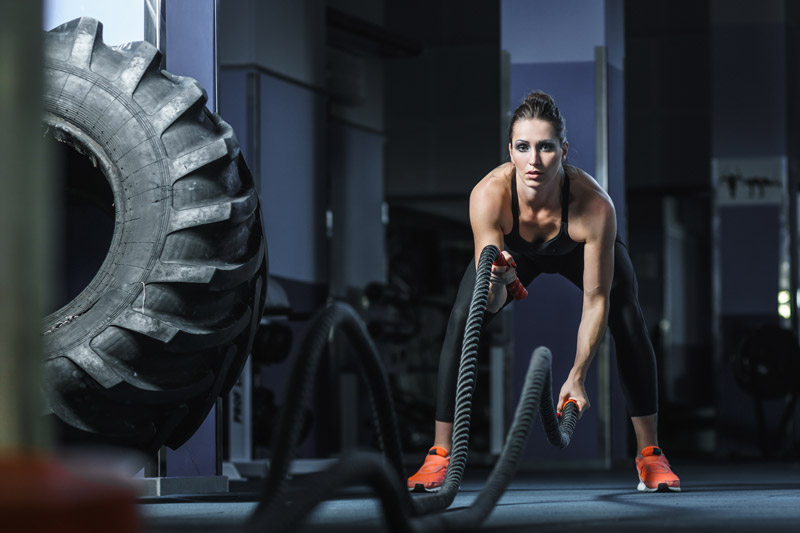 Female Athlete Working Out With Battle Ropes